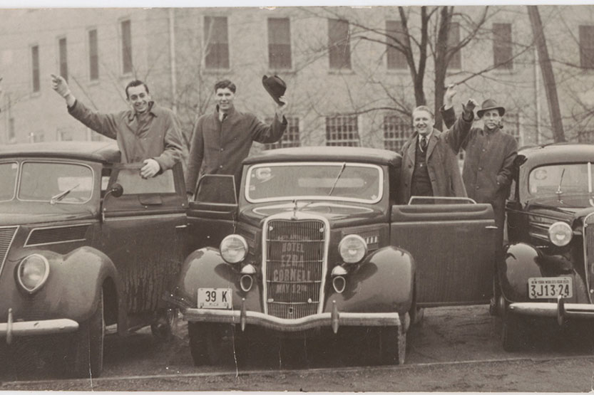 Old photo of Cornellians tipping their hats to the photographer next to their car