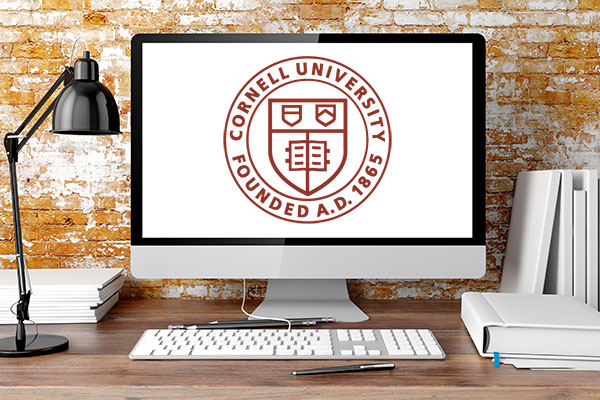 Computer screen on a desk, displaying the Cornell University seal on a white screen