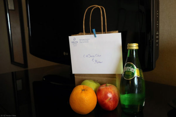 Refreshments and a note attached to a bag in front of a hotel-room TV