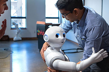 Pepper the robot hugs a student