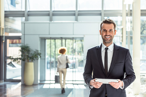Photo of a man standing in a lobby holding a tablet