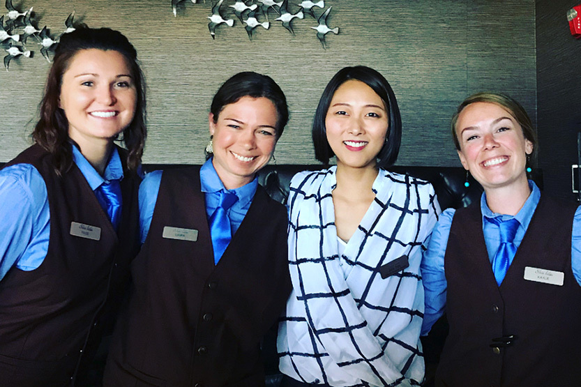 Four students in business attire at Statler's front desk