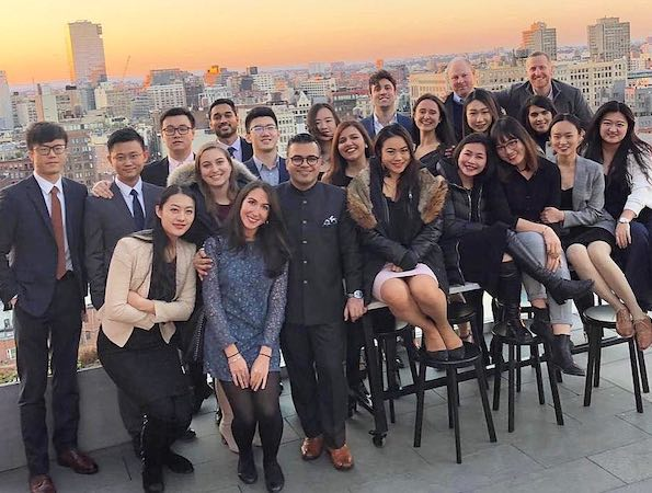 Students on a rooftop with the NYC skyline behind them