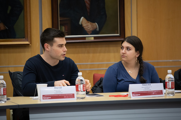 A male and a female student sit behind a table.