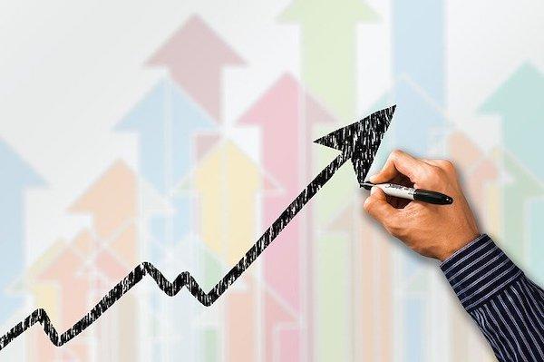 A man draws an upward profit arrow on a whiteboard