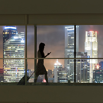 Silhouette of woman walking with luggage. Lit up cityscape in the background.