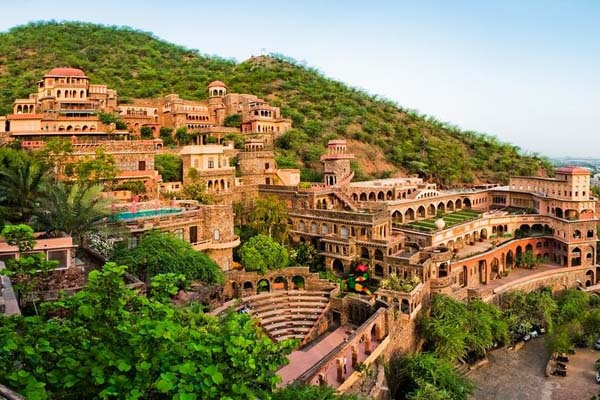 Exterior photo of the Neemrana Fort-Palace resort property. The photo depicts an imposing fort-like structure built into a lush hillside.