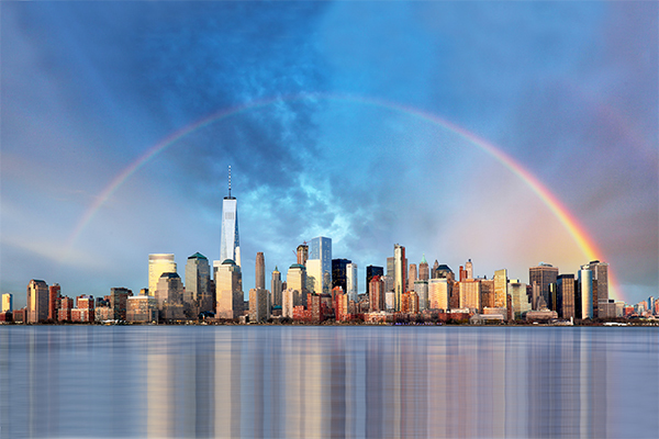photo of New York City skyline with water in the foreground and a rainbow in the blue sky above the buildings