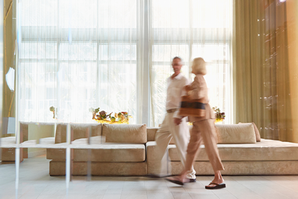 A man and a woman walk through the lobby of a hotel