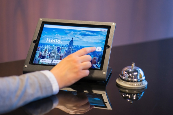 A person checks into a hotel using a tablet.