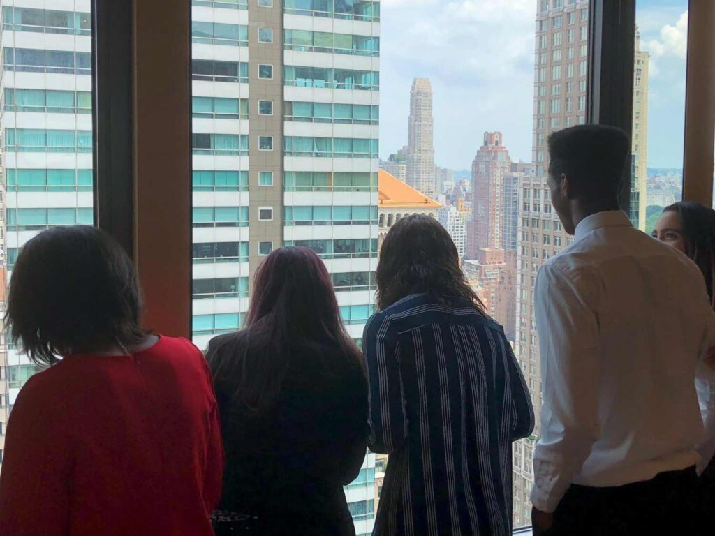 The back of four students as they stand and look out a window