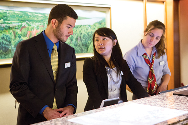 Three people working behind the front desk of The Statler Hotel