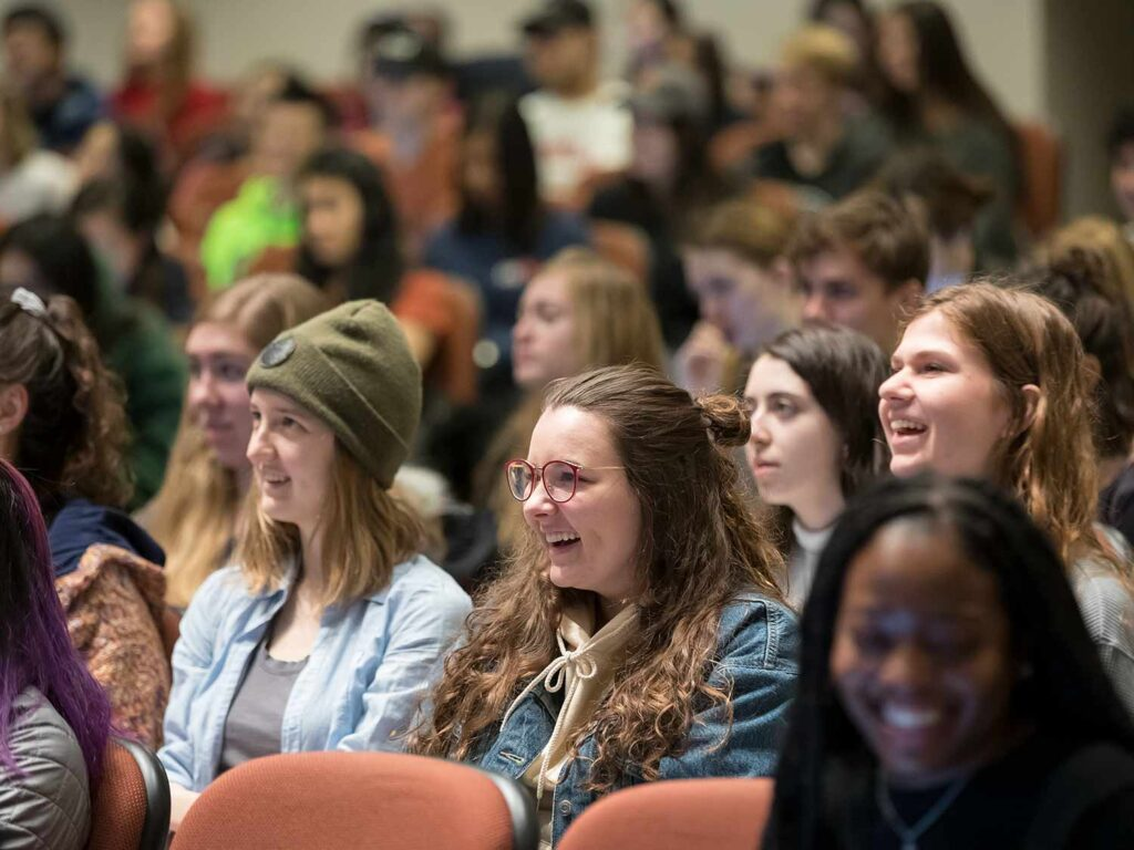 Students smiling in a auditorium