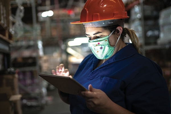 Person wearing a face mask and hardhat works on a touch screen in a warehouse.