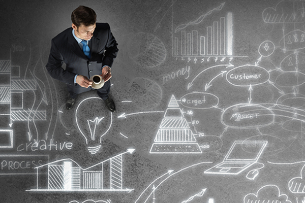 Business person superimposed onto chalkboard-like background with idea bubbles, graphs, charts, technologies, and flow charts, all meant to depict business strategizing.