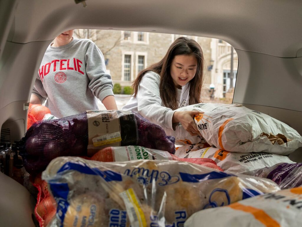 Two SHA students unloading produce from a car trunk