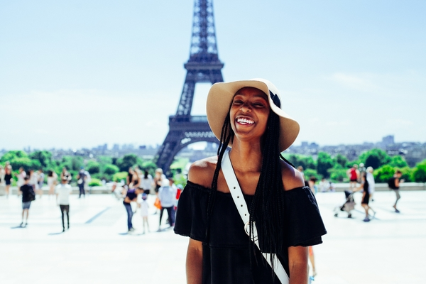 A young woman tourist smiles in front of the Eiffel Tower in Paris, France.